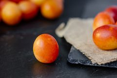 Fresh and ripe wild plum or cherry-plum on black surface. Stock Photos