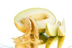 Yellow sliced melon with seeds on white mirror background isolated close up royalty free stock photo