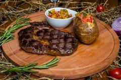 Fresh roast beef meat ribeye steak on wooden plate royalty free stock image