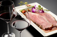 Fresh roasted beef with glass of red wine on white plate with he Stock Images
