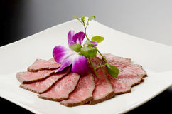 Fresh roasted beef on white plate with herbs in restaurant Royalty Free Stock Photography