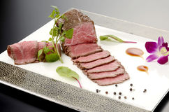 Fresh roasted beef on white plate with herbs in restaurant Stock Photography