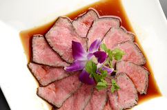 Fresh roasted beef on white plate with herbs in restaurant Stock Photo