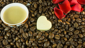 Fresh roasted coffee beans with a cup of coffee, roses leaves Royalty Free Stock Image