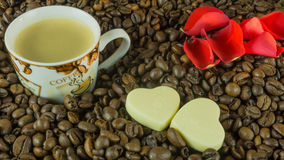 Fresh roasted coffee beans with a cup of coffee, roses leaves Royalty Free Stock Photo