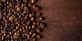 Fresh roasted coffee beans on natural dark oak wood panorama bac stock photos