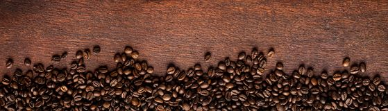 Fresh roasted coffee beans on natural dark oak wood panorama bac royalty free stock images