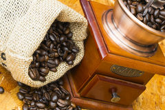 Fresh roasted coffee beans and old coffee grinder. Fresh roasted coffee beans in a small scrotum and old wooden manual coffee grinder Royalty Free Stock Photography