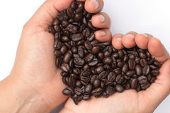 Fresh roasted coffee beans pouring in heart hands Royalty Free Stock Photo