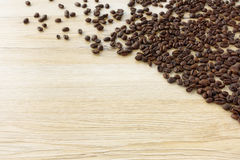 Fresh roasted coffee beans spread out on wooden background Stock Photography