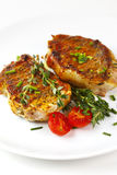 Fresh roasted pork steaks on white plate Royalty Free Stock Images