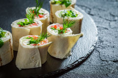 Fresh rolls with salmon, cheese and vegetables for a brunch. On black rock Royalty Free Stock Photos