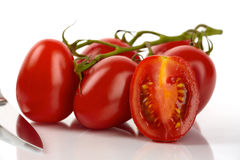 Fresh Roma tomatoes. With a knife in front of white background Royalty Free Stock Photography