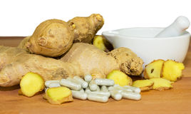 Fresh root ginger. With whole and sliced rhizomes alongside a white ceramic pestle and mortar and a pile of capsules conceptual of plant extracts and Royalty Free Stock Image