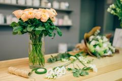 Fresh rose bouquet composition in flower boutique. Nobody. Floral business, florist workplace in shop stock photography