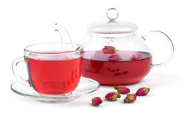 Fresh rose tea. Fresh brewed rose tea in a glass teapot and a cup and a few buds of a tea rose isolated on white background stock photo