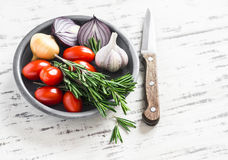 Fresh rosemary, cherry tomatoes, red onion and garlic in a ceramic bowl. On bright wooden background Royalty Free Stock Photography