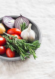 Fresh rosemary, cherry tomatoes, red onion and garlic on a ceramic plate. On a light background Royalty Free Stock Photography