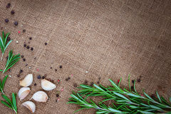Fresh rosemary, garlic and spices on sackcloth background. Fresh rosemary, garlic and black pepper on sackcloth background Stock Images