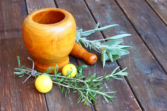 Fresh rosemary herbs in wooden pestle and mortar on wooden table. Fresh rosemary herbs in wooden pestle and mortar Stock Photos