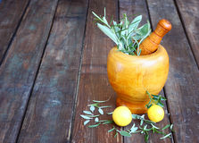 Fresh rosemary herbs in wooden pestle and mortar on wooden table Stock Image