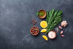Fresh rosemary and mixed spices on black stone table top view. Ingredients for cooking. Food background. Fresh rosemary and mixed spices on black stone table royalty free stock photography