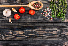 Fresh rosemary, salt, pepper, garlic and a spoon on a black wood. En background, top view Stock Photography