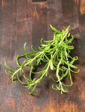 Fresh rosemary sprigs. On wooden background Stock Photography