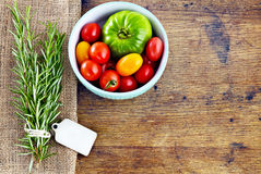 Fresh rosemary with tag, red and green tomatoes on rustic wooden Stock Images