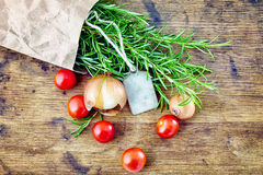 Fresh rosemary with tag, red and green tomatoes on rustic wooden Royalty Free Stock Photos