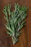 Fresh rosemary on a wooden table, top view, selective focus Stock Photos
