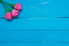 Fresh roses flowers in ray of light on turquoise painted wooden background. Selective focus. Place for text. Fresh roses flowers in ray of light on turquoise Stock Photo