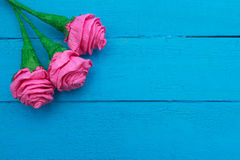 Fresh roses flowers in ray of light on turquoise painted wooden background. Selective focus. Place for text. Fresh roses flowers in ray of light on turquoise Royalty Free Stock Images