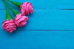 Fresh roses flowers in ray of light on turquoise painted wooden background. Selective focus. Place for text. Fresh roses flowers in ray of light on turquoise Royalty Free Stock Image
