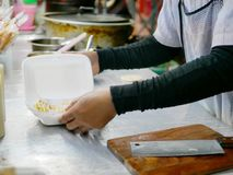 Fresh roti in a box with sweetened condensed milk added on top. Being prepared - delicious street food in Thailand royalty free stock photography