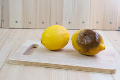 Fresh and rotten lemon put on chopping block Stock Photo