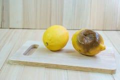 Fresh and rotten lemon put on chopping block Royalty Free Stock Photography