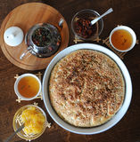 Fresh round focaccia bread with sesame in ceramic form. Serving on a wooden table. Herbal tea, cups, jam Stock Images