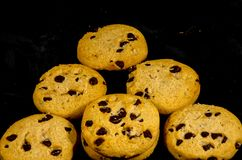 Fresh round sweet chocolate chip cookie`s in the dark. A cookie is a baked or cooked food that is small, flat and sweet. It usually contains flour, sugar and Royalty Free Stock Photo