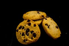 Fresh round sweet chocolate chip cookie`s in the dark. A cookie is a baked or cooked food that is small, flat and sweet. It usually contains flour, sugar and Royalty Free Stock Photography