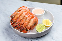 Fresh royal prawns with lemon and sauce. Served with the crushed ice Stock Image