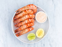 Fresh royal prawns with lemon and sauce. Served with the crushed ice Royalty Free Stock Photography