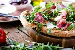 Fresh Rucola Pizza with parma ham on wooden cuting board. royalty free stock photography