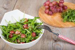 Fresh rucola salad with red grapes Stock Photo