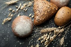 Fresh rustic bread with grains on a black table with spikelets of wheat and oats stock images