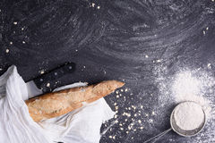 Fresh rustic bread wrapped in white towel with flour and knife on dark background. Top view, space for text. Stock Image