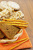 Rye bread and crispbreads in a wicker plate. Fresh rye bread, bread sticks, and various crispbreads in a wicker tray and the orange napkin against a wooden board stock images