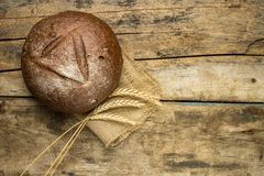 Fresh rye bread with ears on wooden table Royalty Free Stock Image