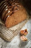 Fresh rye sliced bread on natural linen napkin and garlic cloves on rustic wooden background. Vertical royalty free stock photo
