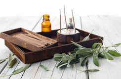 Fresh sage leaves with spa aromatherapy kit. Sage leaves and wooden box with aromatherapy oils and incense sticks on wooden background stock photo